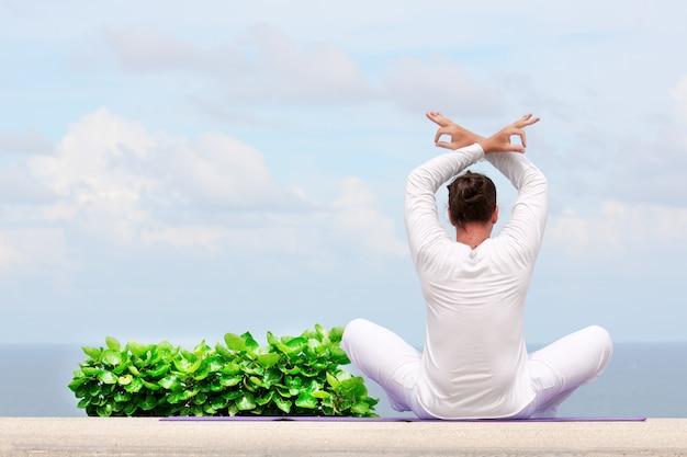 Uomo caucasico in abiti bianchi che medita yoga sul molo o sulla piattaforma della riva del mare