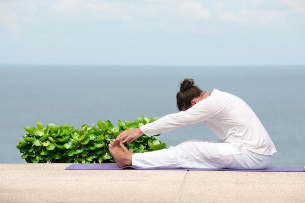 Uomo caucasico in abiti bianchi che medita yoga sul molo della riva del mare sea