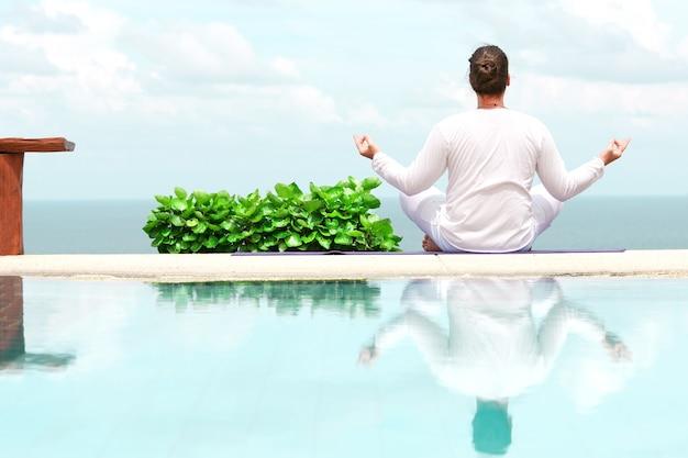 Uomo caucasico in abiti bianchi che medita yoga sul molo in riva al mare