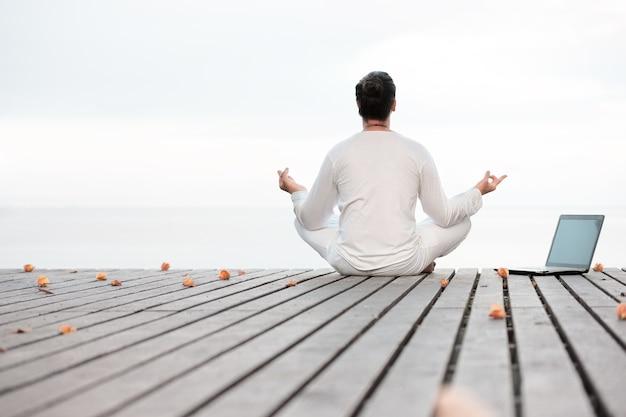 Uomo caucasico in abiti bianchi che medita yoga con il computer portatile sulla piattaforma del molo in legno