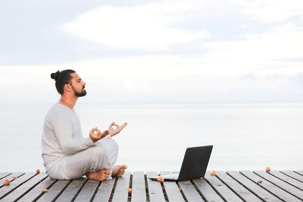 Uomo caucasico in abiti bianchi che medita yoga con il computer portatile sul molo di legno