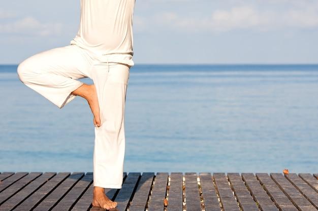 Uomo caucasico in abiti bianchi che medita yoga sul molo di legno