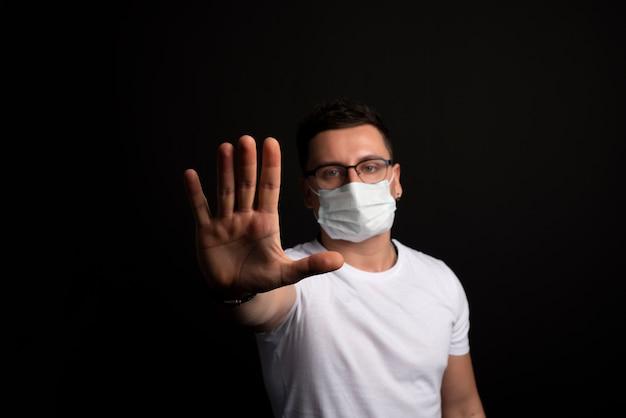 Uomo caucasico in maglietta bianca con maschera usa e getta che mostra un segnale di stop
