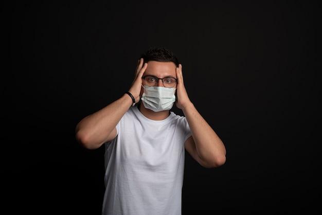 Uomo caucasico in maglietta bianca con maschera usa e getta.