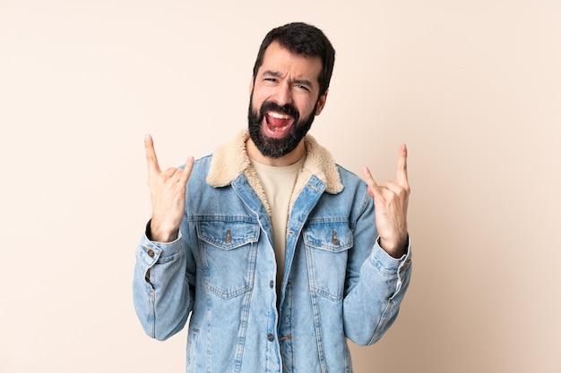 Uomo caucasico con la barba su sfondo isolato che fa il gesto del corno