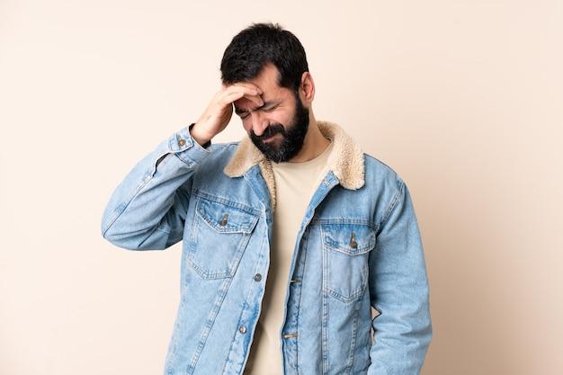 Uomo caucasico con la barba su sfondo isolato con mal di testa