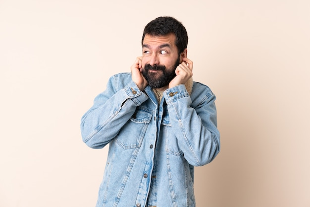 Uomo caucasico con la barba sopra la parete isolata frustrata e che copre le orecchie