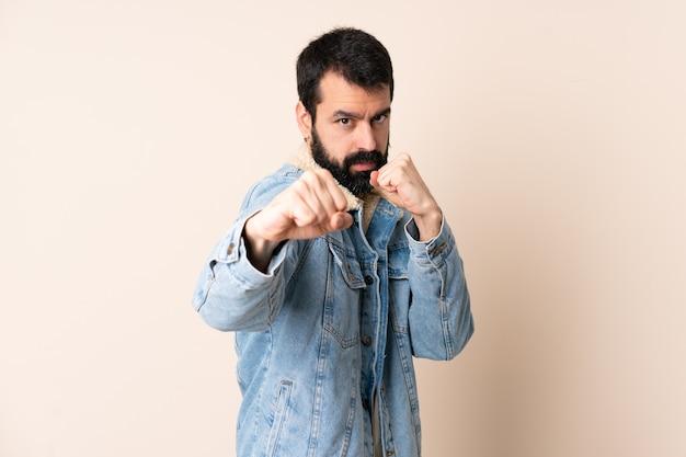 Uomo caucasico con la barba sopra la parete isolata con gesto di combattimento