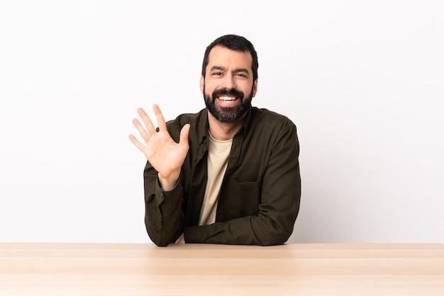 Uomo caucasico con la barba in una tabella che conta cinque con le dita