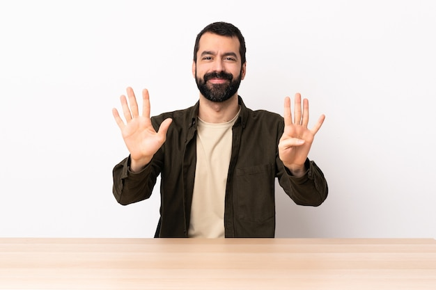 Uomo caucasico con la barba in una tabella che conta nove con le dita.