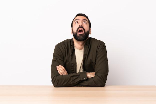 Uomo caucasico con la barba in una tabella che osserva in su e con l'espressione sorpresa