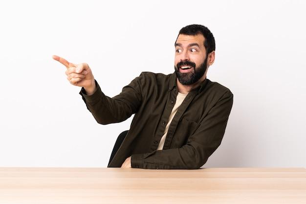 Uomo caucasico con la barba in una tabella che punta lontano