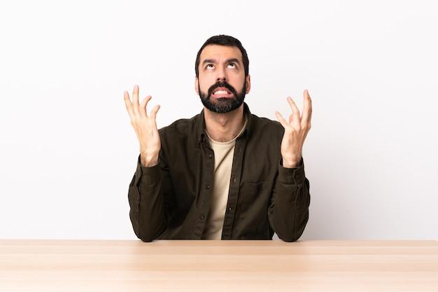 L'uomo caucasico con la barba in una tabella ha sottolineato sopraffatto.