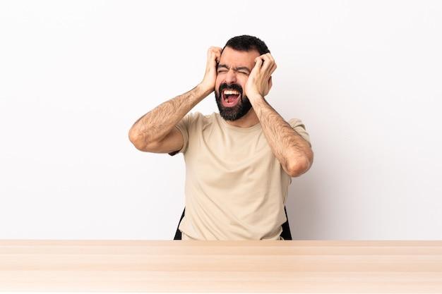 L'uomo caucasico con la barba in una tabella ha sottolineato sopraffatto