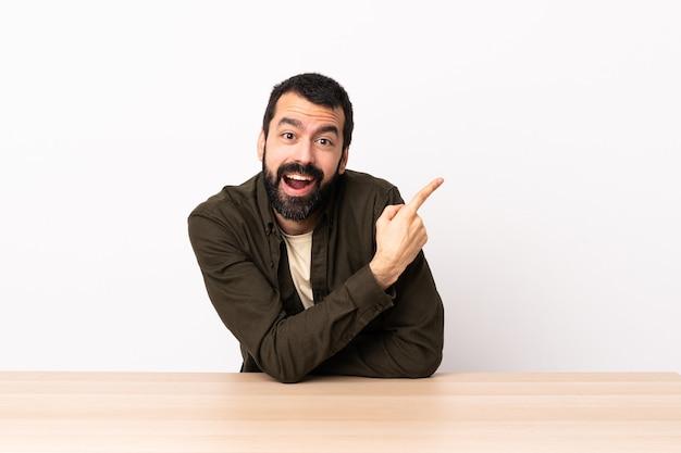 Uomo caucasico con la barba in un tavolo sorpreso e indicando il lato.