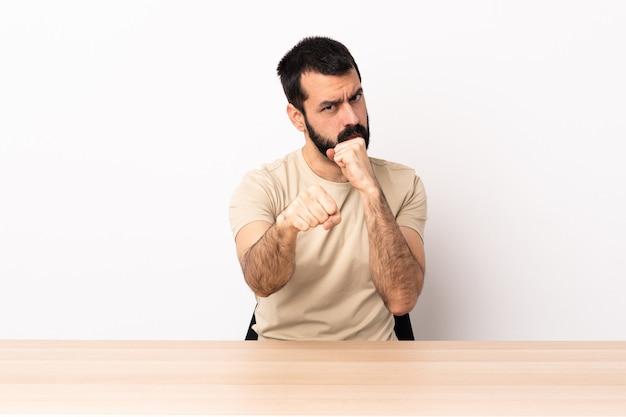 Uomo caucasico con la barba in un tavolo con gesto di combattimento.