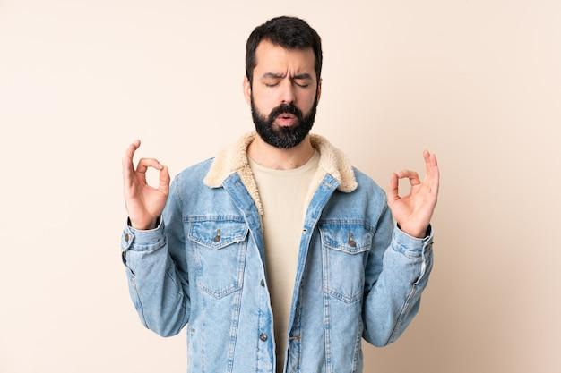 Uomo caucasico con la barba sopra la parete nella posa di zen