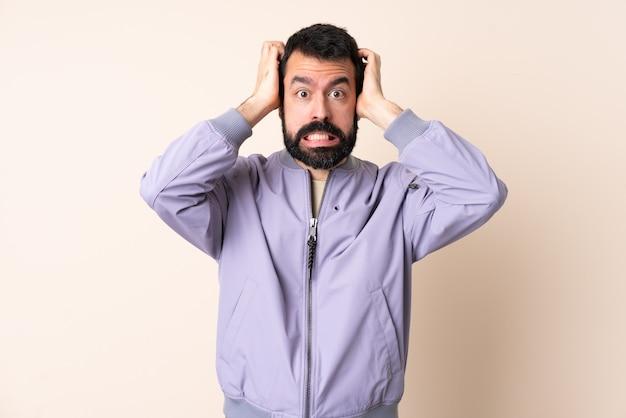 Uomo caucasico con la barba che indossa una giacca su sfondo isolato facendo gesto nervoso