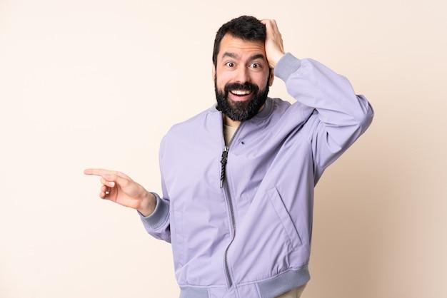 Uomo caucasico con la barba che indossa una giacca sopra il muro isolato sorpreso e puntando il dito di lato