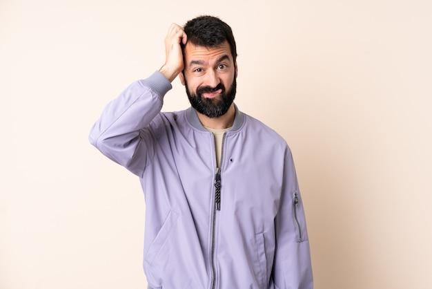 Uomo caucasico con la barba che indossa una giacca sopra il muro isolato con un'espressione di frustrazione e non comprensione