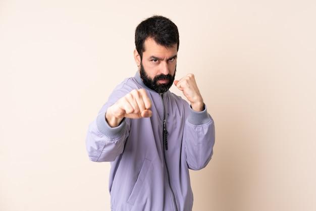 Uomo caucasico con la barba che indossa una giacca sopra isolato con gesto di combattimento