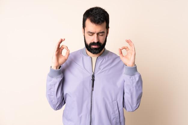 Uomo caucasico con la barba che indossa una giacca sopra il muro in posa zen