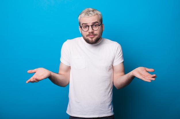 L'uomo caucasico con barba e capelli biondi sta gesticolando indecisione con le palme su una parete blu dello studio
