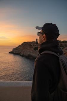 Uomo caucasico con un cappello e occhiali da sole guardando l'orizzonte nel mare accanto a una scogliera a palma de mallorca, spain