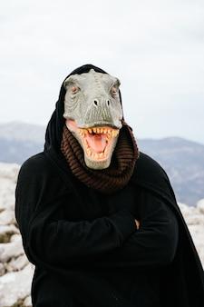 Uomo caucasico con una maschera di dinosauro e un capo facendo un gesto arrabbiato con il suo corpo nella sierra de tramuntana, palma de mallorca, spagna