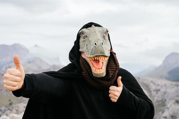 Uomo caucasico con una maschera di dinosauro e un capo facendo il gesto ok con le mani nella sierra de tramuntana, palma de mallorca, spagna