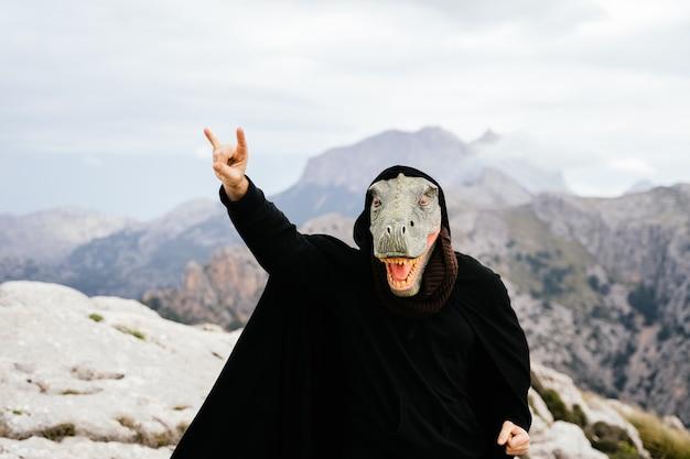 Uomo caucasico con una maschera di dinosauro e un mantello che fa il segno delle corna con la sua mano nella sierra de tramuntana, palma de mallorca, spagna
