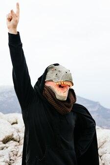 Uomo caucasico con una maschera di dinosauro e un capo alzando la mano per porre una domanda nella sierra de tramuntana, palma de mallorca, spagna