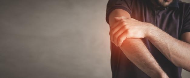 Uomo caucasico con dolore al gomito. concetto di sollievo dal dolore