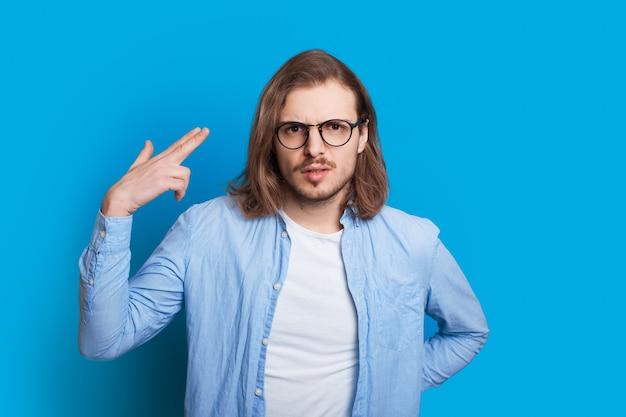 Uomo caucasico con capelli lunghi e occhiali da vista che gesticolano con la mano come sparare