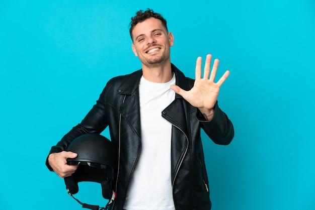 Uomo caucasico con un casco da motociclista isolato su sfondo blu, contando cinque con le dita