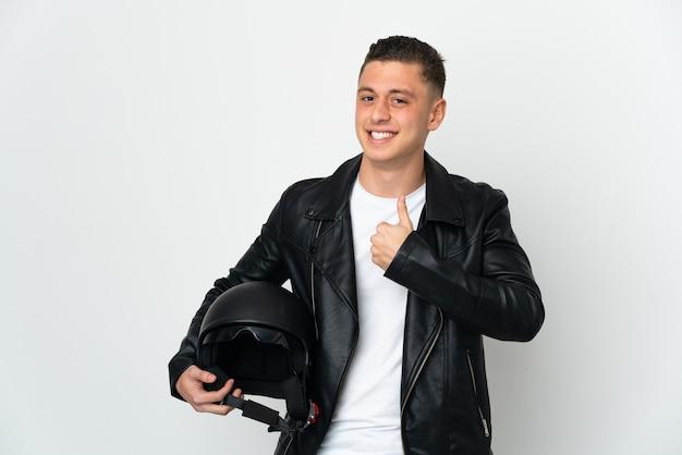 Uomo caucasico con un casco da motociclista isolato su sfondo bianco che fa un gesto di pollice in alto