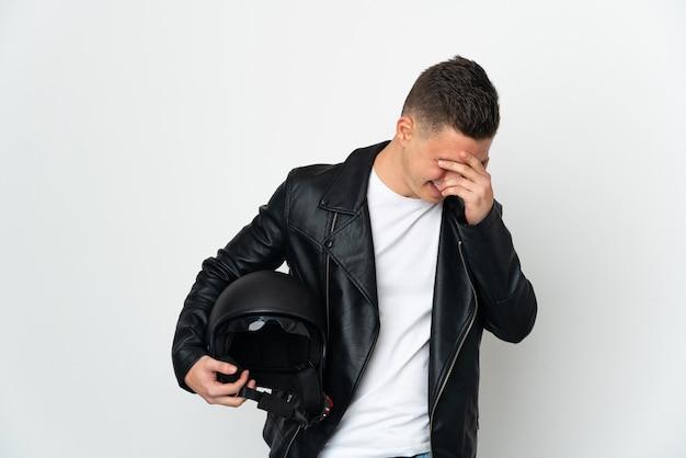 Uomo caucasico con un casco da motociclista isolato sul muro bianco ridendo