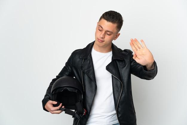 Uomo caucasico con un casco da motociclista isolato sul muro bianco che fa gesto di arresto e deluso