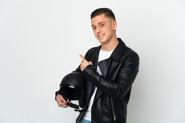 Uomo caucasico con un casco da motociclista isolato sulla parete bianca che punta indietro