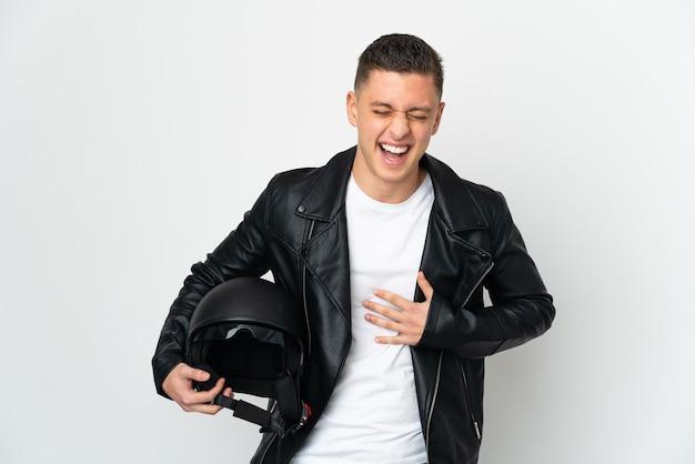 Uomo caucasico con un casco da motociclista isolato sul muro bianco che sorride molto