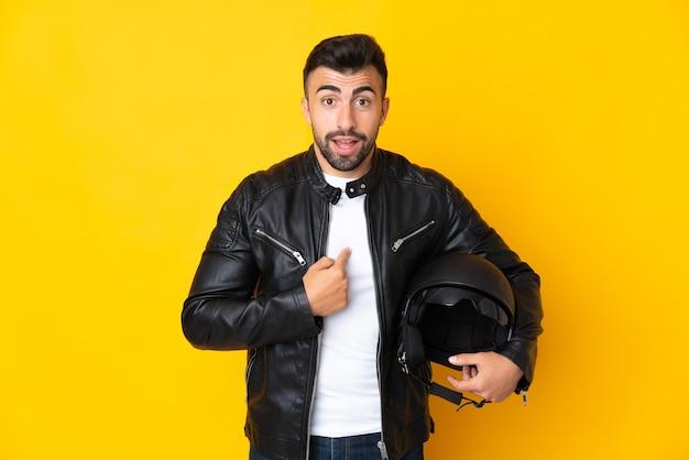 Uomo caucasico con un casco da motociclista sopra la parete gialla isolata con l'espressione facciale di sorpresa