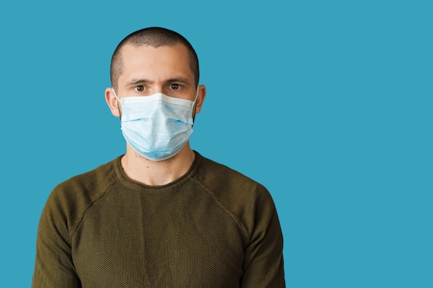 L'uomo caucasico con una maschera medica bianca sul viso guarda davanti su una parete blu con spazio libero