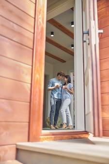 Uomo e donna caucasici mentre bevono caffè al mattino in una casa moderna di lusso