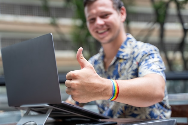 Uomo caucasico che lavora su un laptop mentre fa cenno di stare bene con il dito che indossa un braccialetto lgtb