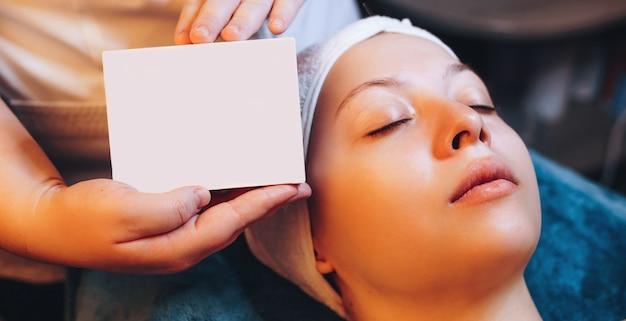 Massaggiatore caucasico che mostra un foglio di spazio vuoto in piedi vicino a una donna con gli occhi chiusi che ha una sessione di massaggio