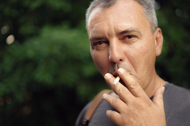 Sigaretta di fumo dell'uomo invecchiato centrale maturo caucasico all'aperto. dipendenza da nicotina. copia spazio