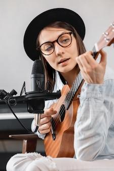 Donna caucasica millenaria in un cappello con un microfono, suonare la chitarra o l'ukulele