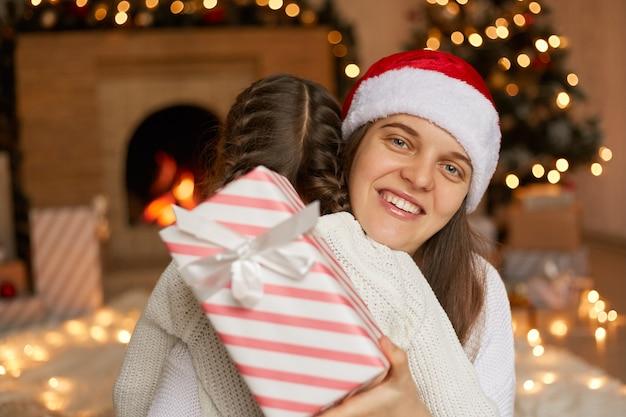 La mamma caucasica ringrazia il suo bambino per la confezione regalo, abbraccia la figlia, in posa vicino all'albero di natale a casa