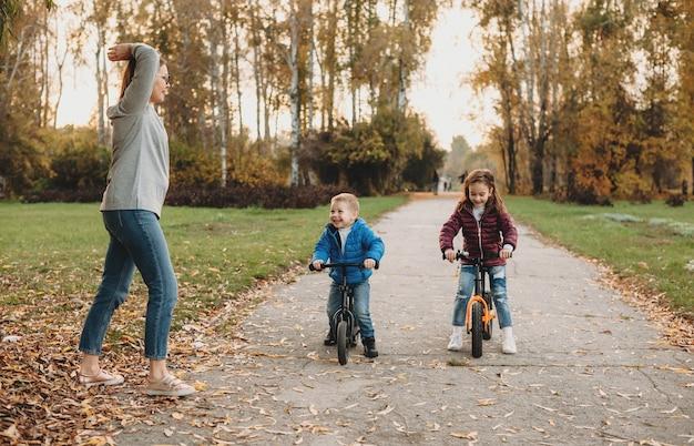 Madre caucasica che dà inizio ai suoi figli che stanno andando in bicicletta in una soleggiata giornata autunnale
