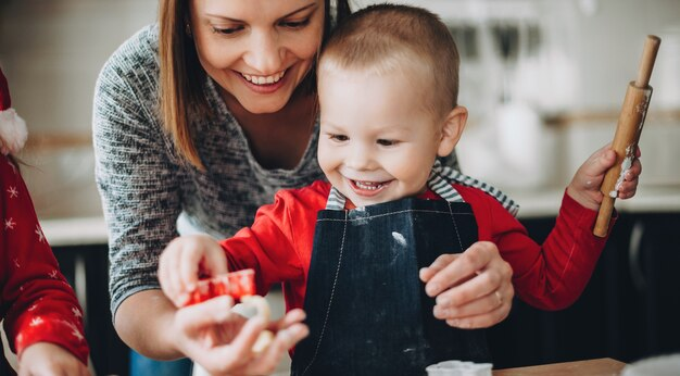 Madre caucasica che aiuta suo figlio a rotolare la pasta